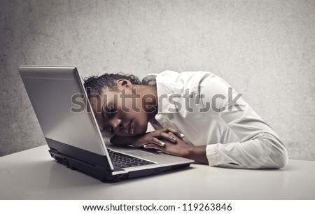 Black girl sleeping on a laptop computer - stock photo