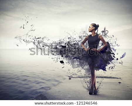 Black girl, with a black dress which becomes paint, standing on a pier - stock photo