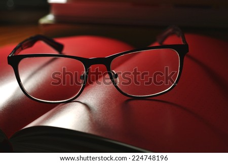 black glasses and red book with pages - stock photo
