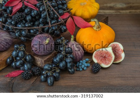 Black grapes in a basket and ripe figs, red raspberries, orange pumpkin and blackberries with autumn leaves on the wooden background - stock photo