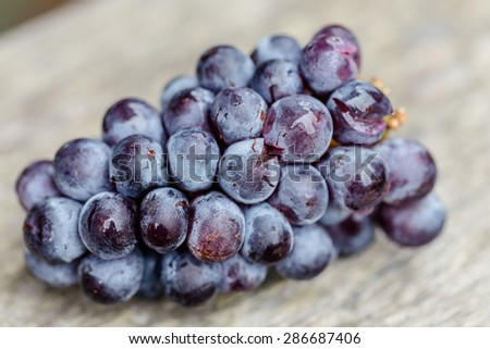 Black grapes isolated on wooden  - stock photo