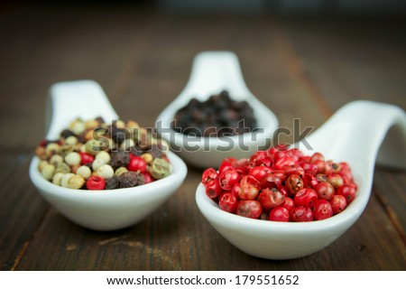 Black, green and pink pepper in spoon on a wooden table - stock photo