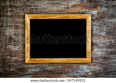 Black grunge background with many white scratches. Wood texture inside. Wooden frame with black fill, great for text, menu, adverts. - stock photo