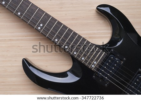 black guitar on the background of wood texture - stock photo