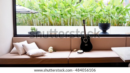 black guitar, white rose and white pillow are living on cream sofa at living room.