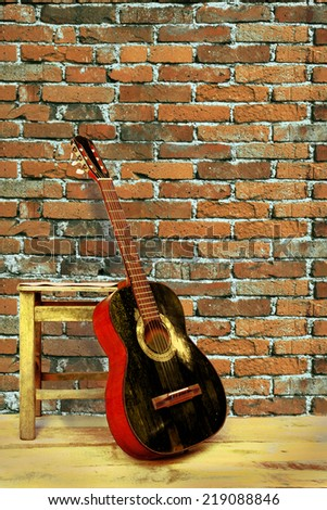 black guitar with brick wall