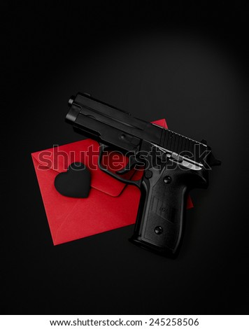 black gun black heart on a red envelope black background - stock photo