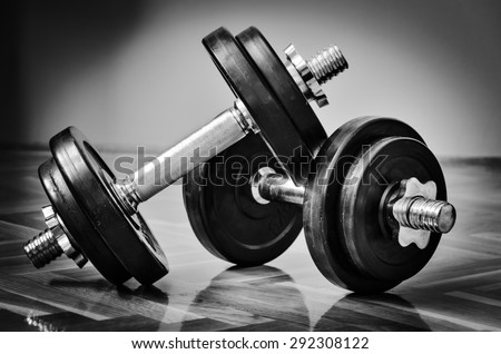 Black gym dumbbell with disks, black and white photo - stock photo