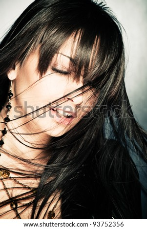 black hair woman with hair in motion, eyes closed, studio shot - stock photo