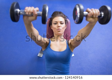 Black-haired woman energetically lifting weights - stock photo