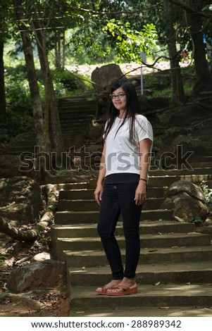 Black haired woman in a public forest.