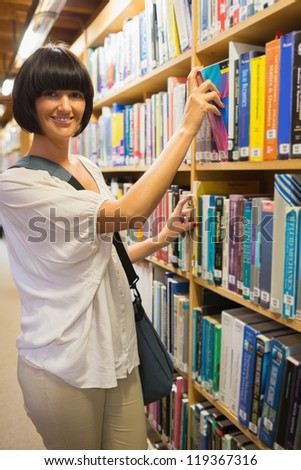Black-haired woman taking a book out of the shelves in the library - stock photo