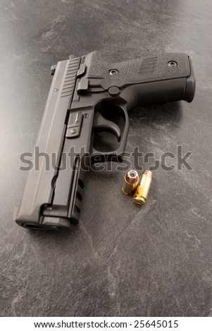 Black hand gun or semi automatic pistol on black textured surface with hollow point personal defense bullets. - stock photo