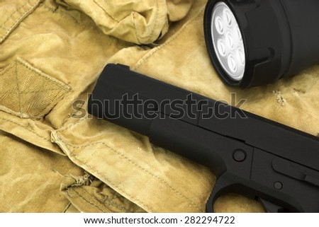 Black Handgun And  Turned On Led Tourch On The  Faded Green Backpack Background Close-up - stock photo