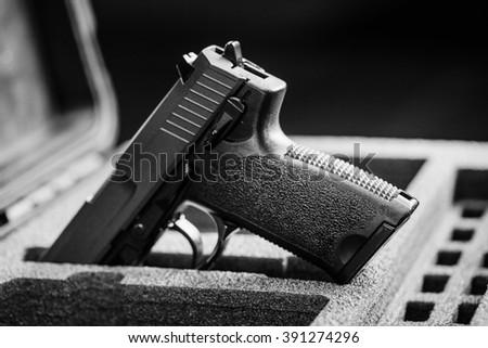 black handgun in plastic Secure Storage Case - stock photo