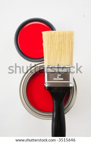 Black handle paint brush on top of red paint with and without lid