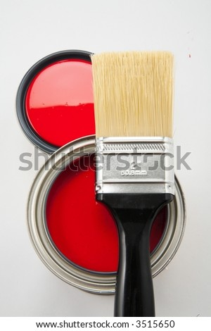 Black handle paint brush on top of red paint with and without lid - stock photo