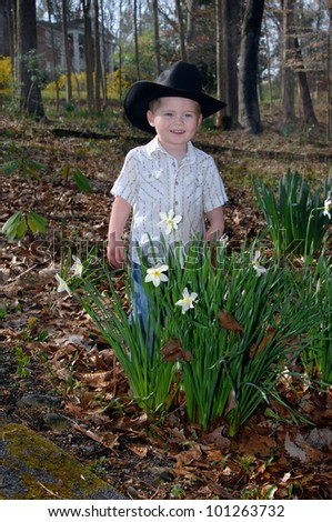 Black hat, jeans and snap up shirt makes this little boy feel like a cowboy.  He is standing besides blooming daffodils and is smiling. - stock photo