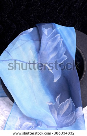 Black hat with a blue scarf with a rose motif on a marble table, fashion - stock photo