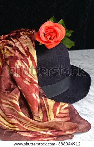 Black hat with a scarf with a tiger motif of red rose on a marble table, fashion - stock photo