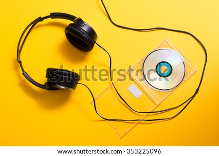 Black headphones with CD disc on yellow background - stock photo