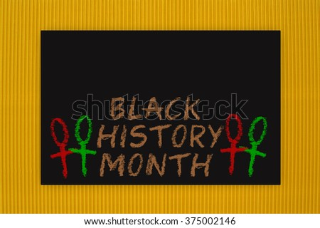 Black History Month Blackboard hanging on yellow textured background pattern - stock photo