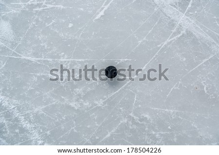 black hockey puck on ice rink. - stock photo