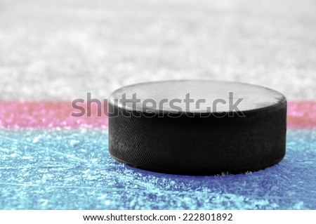 black hockey puck on ice rink  - stock photo