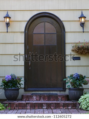 Black home door with arched top with two lanterns - stock photo