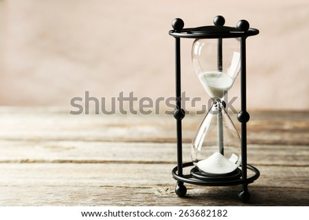 Black hourglass on grey wooden background