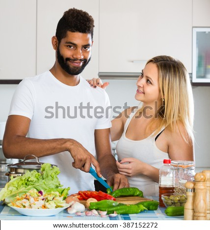 Black husband helping white wife preparing healthy dinner