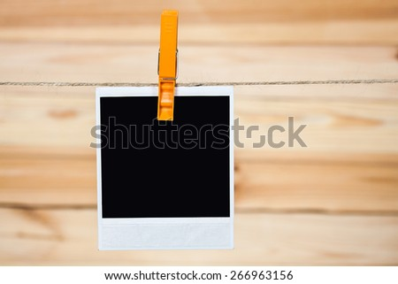 Black instant photo, hanging on the clothesline on wooden background. - stock photo