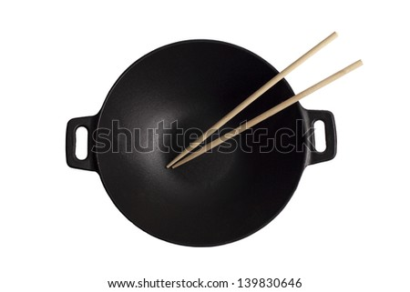 Black iron cast wok with chopsticks isolated on white background - stock photo
