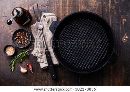 Black iron empty grill pan, seasonings and meat fork on wooden texture background - stock photo