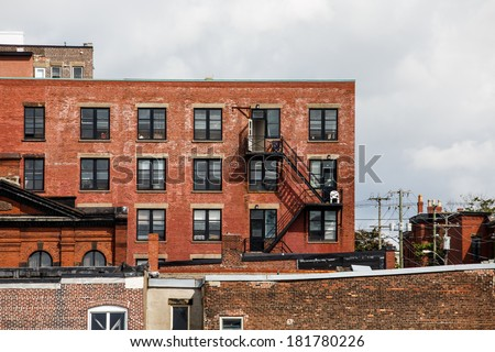 Black iron fire escapes on old brick buildings in Canada - stock photo