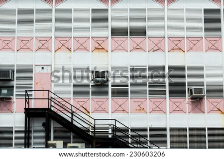 Black iron stairs on an old pink and white building in the Bahamas - stock photo