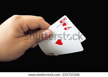 Black Jack two card of heart in playing cards game in the hand on a black background - stock photo