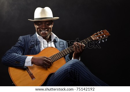 Black jazz musician wearing suit and white hat playing guitar.