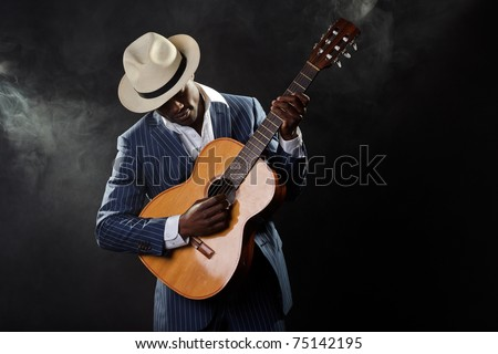 Black jazz musician wearing suit and white hat playing guitar. - stock photo