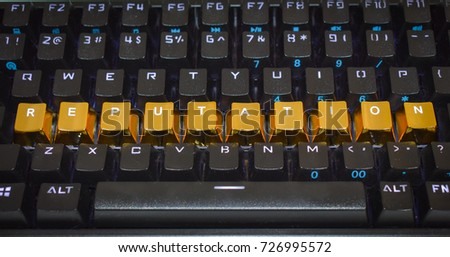 "Black keyboard with the word, ""reputation"" spelled out in gold key caps."