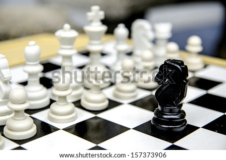 Black knight facing white chess pieces - stock photo