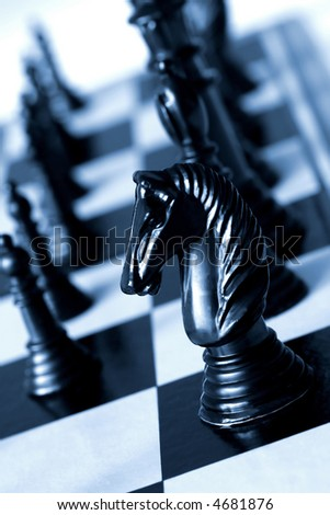 Black knight on a chessboard, in blue duotone.  Shallow depth of field. - stock photo