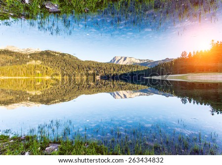 Black lake in Durmitor national park in Montenegro, Balkans, Europe. Dramatic scenery. Beauty world. Flip canvas vertical. Double exposure effect. - stock photo