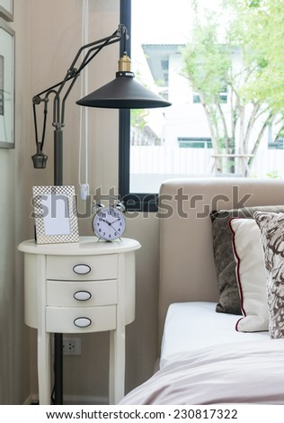 black lamp, picture frame and alarm clock on bedside table - stock photo