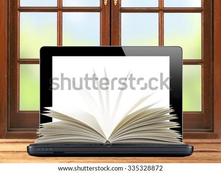 Black laptop and openned book wooden table over window - stock photo