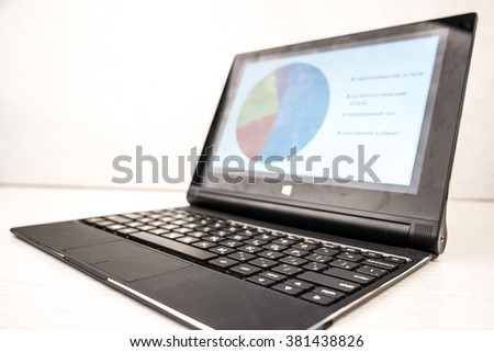 Black laptop with business charts on screen, on white table in office