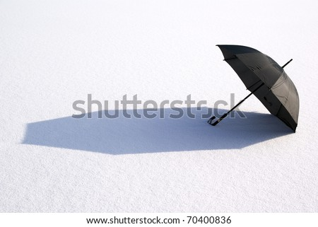 black large umbrella lies on snow in sun - stock photo