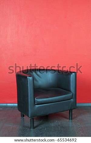 Black leather armchair about a wall - stock photo
