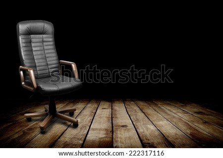 Black leather armchair in dark room. Business interior background - stock photo