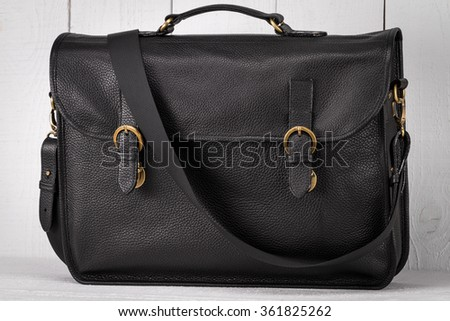 black leather bag on a white wooden background